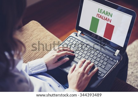 Female learning italian at home with a laptop computer at home. - stock photo