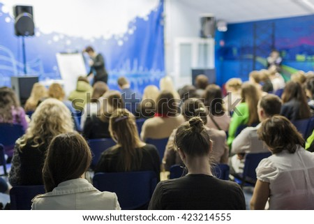 Female Lecturer Speaking In front of the Large Group of People. Horizontal Image Composition