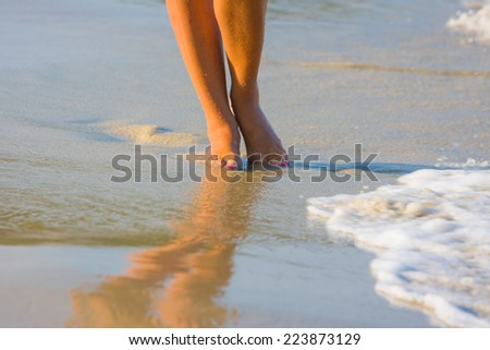 Female leg walking on the beach in the ocean - Narrow depth of field - stock photo