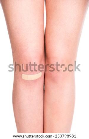 Female leg with adhesive bandage. Close-up. White background. - stock photo