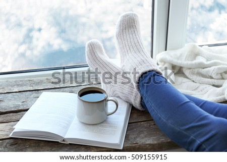 Female legs and hot drink on windowsill