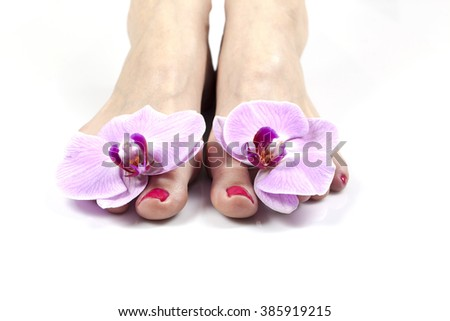 female legs and orchid flowers