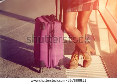 female legs closeup. stylish woman with a suitcase standing at the window at the airport. traveler waiting airplane flight - stock photo