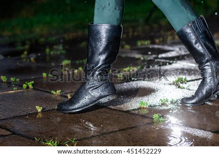 Female legs in black leather high boots on cobble  the edge of rain puddle, closeup. Concept  protection against rainy weather, waterproof footwear