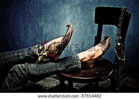 female legs in blue jeans and oriental footwear leaned on chair, indoor shot - stock photo