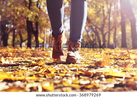 Female legs in boots on autumn leaves - stock photo