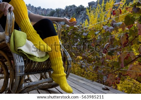 Female Legs in Bright yellow socks sit on a Rocking chair, Close Up ...