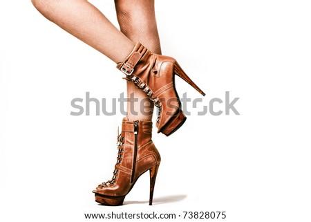 female legs in brown high heel platform shoes, studio shot - stock photo