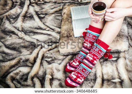 female legs in Christmas socks with a book and a cup of coffee. artificial fur on the floor - stock photo