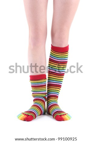 female legs in colorful striped socks isolated on white - stock photo