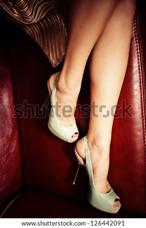female legs in elegant high heel shoes on leather sofa - stock photo