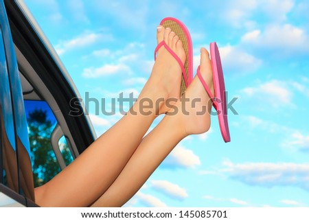Female legs in pink sandals out from the car. Summer trip concept.