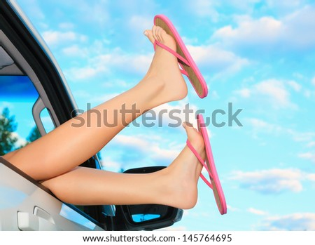 Female legs in pink sandals out from the car. Summer trip concept. - stock photo