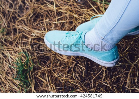 Female legs in sneakers and jeans on the background of dry grass in the Park - stock photo