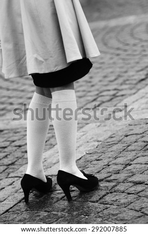 female legs in socks and black shoes on the pavement - stock photo