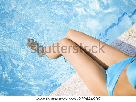 Female legs in the pool water - stock photo