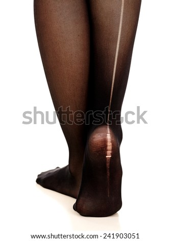 Female legs in torn pantyhose, white background, isolated - stock photo
