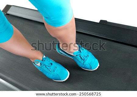 Female legs in turquoise sneakers on a treadmill. Top view - stock photo
