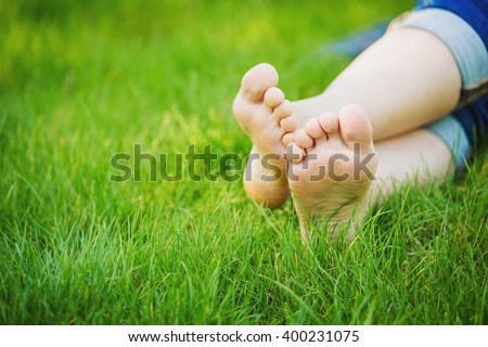 female legs lie on the grass on sunny day  - stock photo