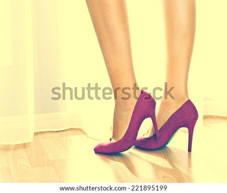 Female legs on a high heels. Standing by the window.