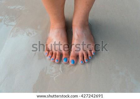 Female legs on beach. top view