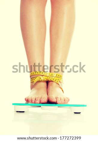 Female legs on scale tied up with measuring tape, isolated on white - stock photo