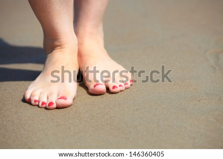 Female legs walking in water, girl's barefoot legs on the sand beach