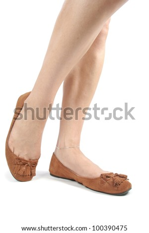 Female legs wearing  brown moccasin flat shoes over white background - stock photo