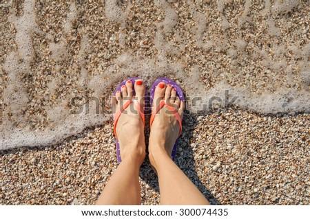 Female legs wearing flip flops near sea. top view - stock photo
