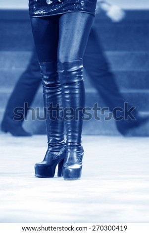 female legs wearing high heeled shoes on the stage