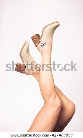 Female Legs Wearing Light Colored Leather Booties - stock photo