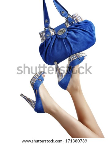 Female legs with blue shoes and handbag  - stock photo