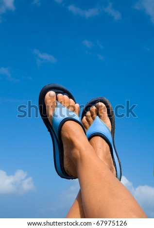 female legs with flip-flops over blue sky - stock photo