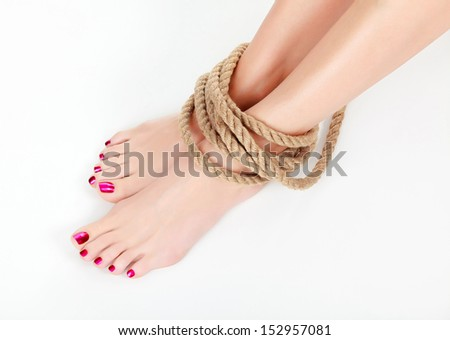 Female legs with thick rope round them  - stock photo