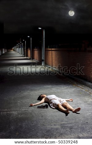 Female lies dead in the street under a night sky - stock photo