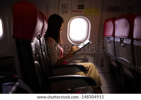 Female lonely traveling on plane while reading on seats during a sunset, lowlight ambience mode  - stock photo