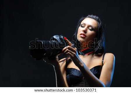 Female looking at a new digital camera with surprise and interest - stock photo