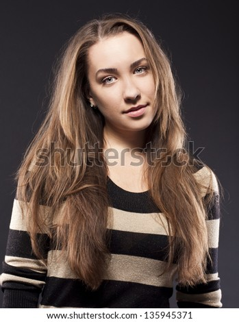 female looking at the camera . striped jacket - stock photo
