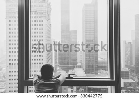 Female looks out over Shanghai from a skyscraper - stock photo