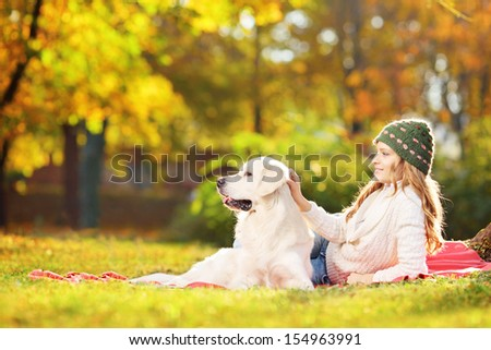 Female lying on a green grass with her labrador retriever dog in a park - stock photo