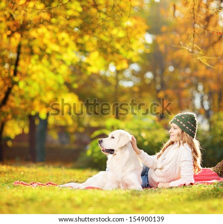 Female lying on a green grass with her labrador retriever dog in a park, shot with a tilt and shift lens - stock photo