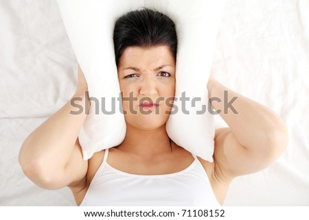 Female lying on bed and closing her ears with pillow.  Insomnia - stock photo