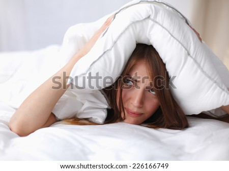 Female lying on bed and closing her ears with pillow, isolated - stock photo