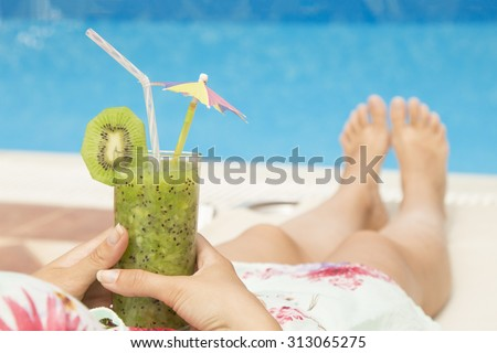 Female lying on sunbed and holding a glass of fresh kiwi smoothie