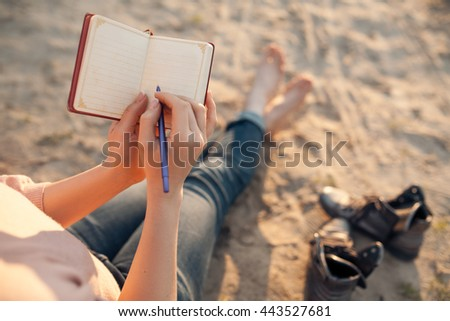 female makes notes and sitting on the beach; woman writes in diary and sitting on sand; - stock photo