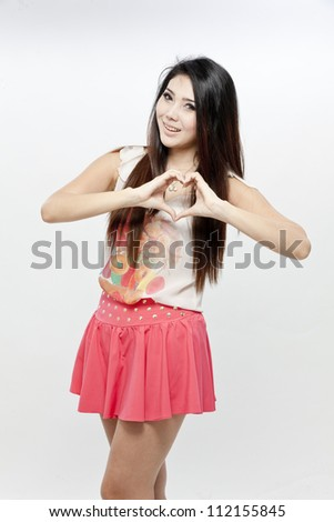 Female making heart shape with her hands - stock photo
