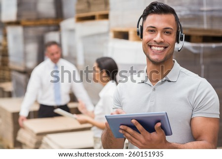 Female manager using digital tablet in warehouse - stock photo