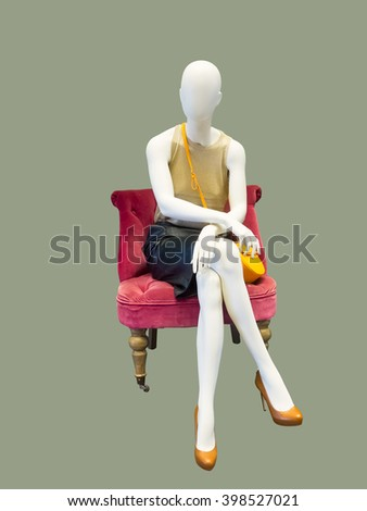 Female mannequin sitting on red armchair, against grey background. No brand names or copyright objects - stock photo