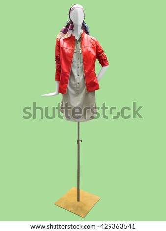 Female mannequin wearing red leather jacket and gray dress. Isolated on green background. No brand names or copyright objects. - stock photo