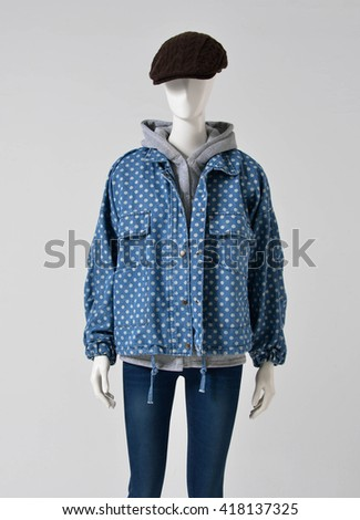 female mannequin with jacket ,cap gray background - stock photo